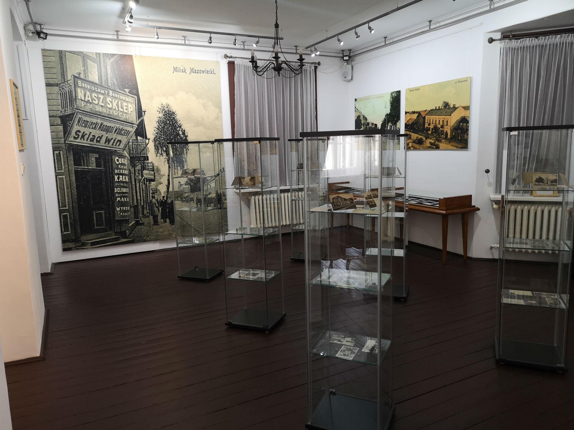 Wnętrze sali wystawowej Muzeum Ziemi Mińskiej. Na podłodze stoją szklane gabloty z trzema półeczkami w każdej, na których wyeksponowane są zabytkowe pocztówki. Na ścianach wiszą wydrukowane reprodukcje wybranych pocztówek.