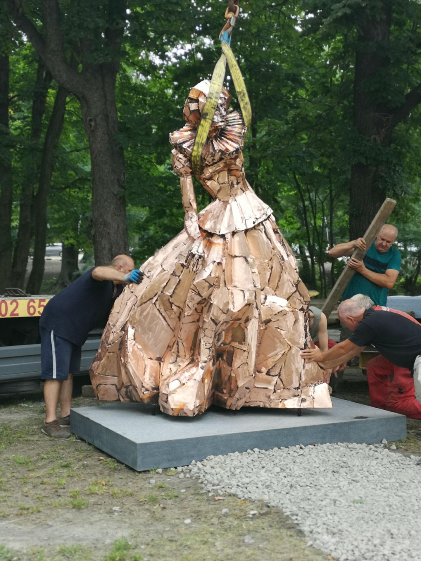 Ustawianie pomnika na cokole. Rzeźbę trzymaną przez dźwig tuż nad ziemią sytuuje we właściwym miejscu trzech mężczyzn.