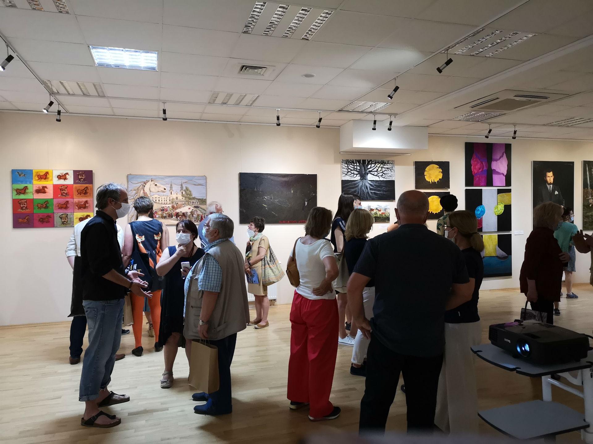 Fotografia wykonana w sali konferencyjno-wystawowej w Miejskiej Bibliotece Publicznej w Mińsku Mazowieckim. Na pierwszym planie widzimy żywo dyskutującą publiczność. W tle ściana z zawieszonymi na niej obrazami.