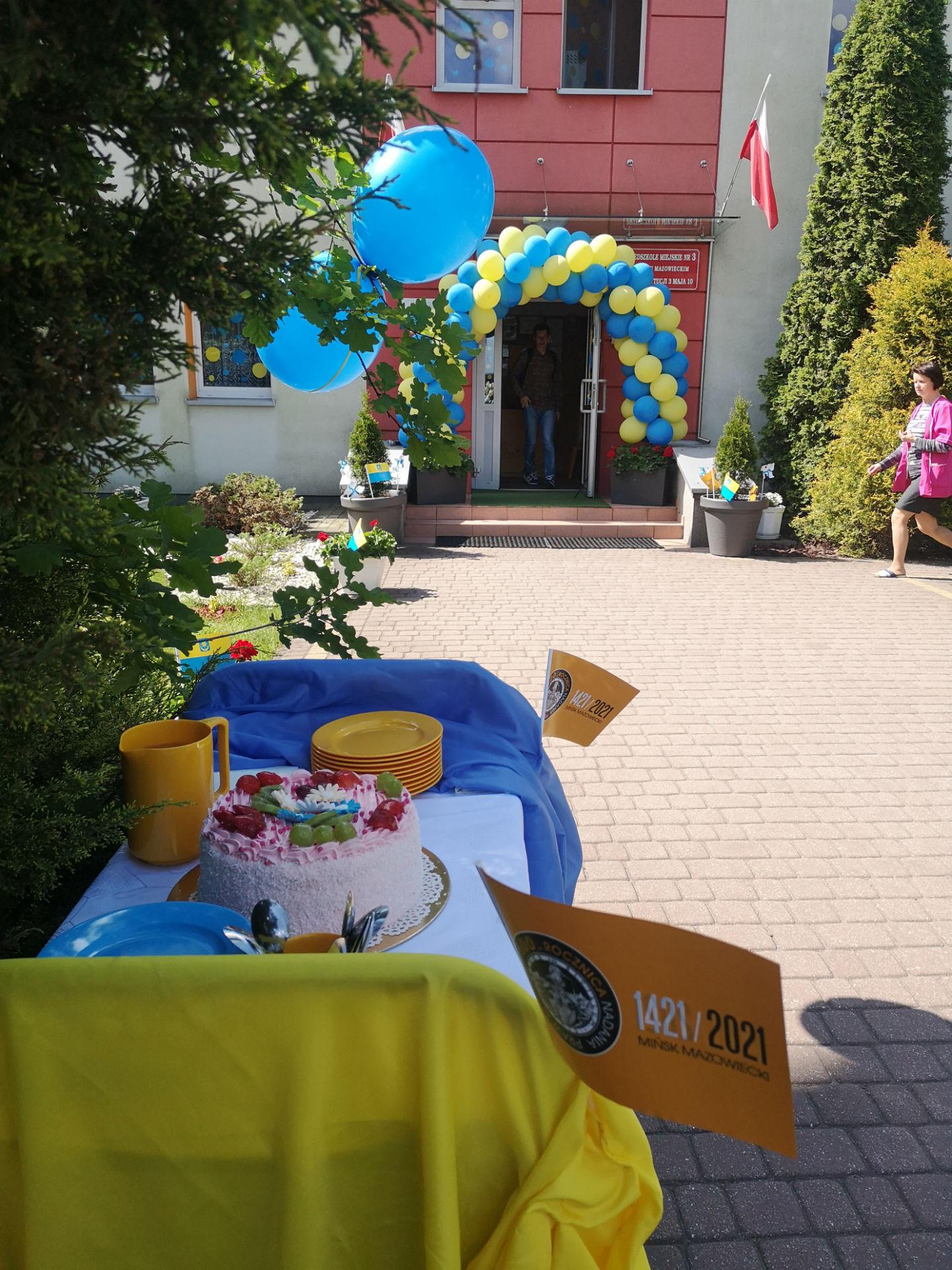Fotografia wykonana przed przedszkolem miejskim nr 3. Na pierwszym planie stół z tortem. W tle wejście do przedszkola. Wszystko udekorowane żółto-niebieskimi balonami oraz chorągiewkami przypominającymi o obchodach 600-lecia miasta.