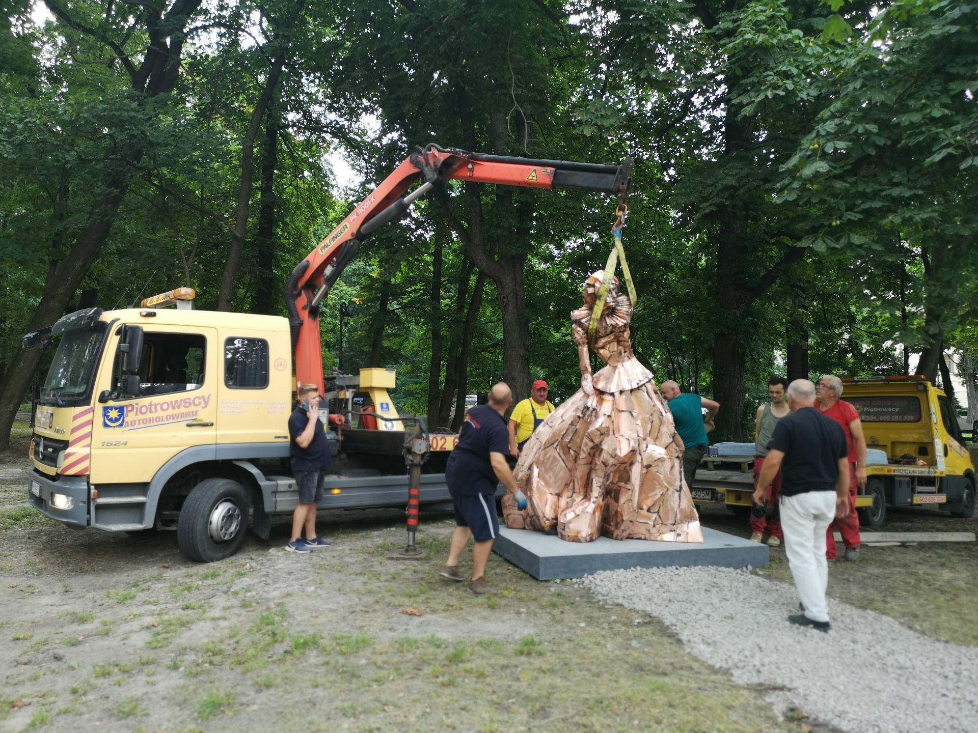 Pomnik postawiony jest już na cokole. Zamocowana jest nad nim specjalna uprząż do dźwigu stojącego za rzeźbą otoczoną przez grupę mężczyzn.