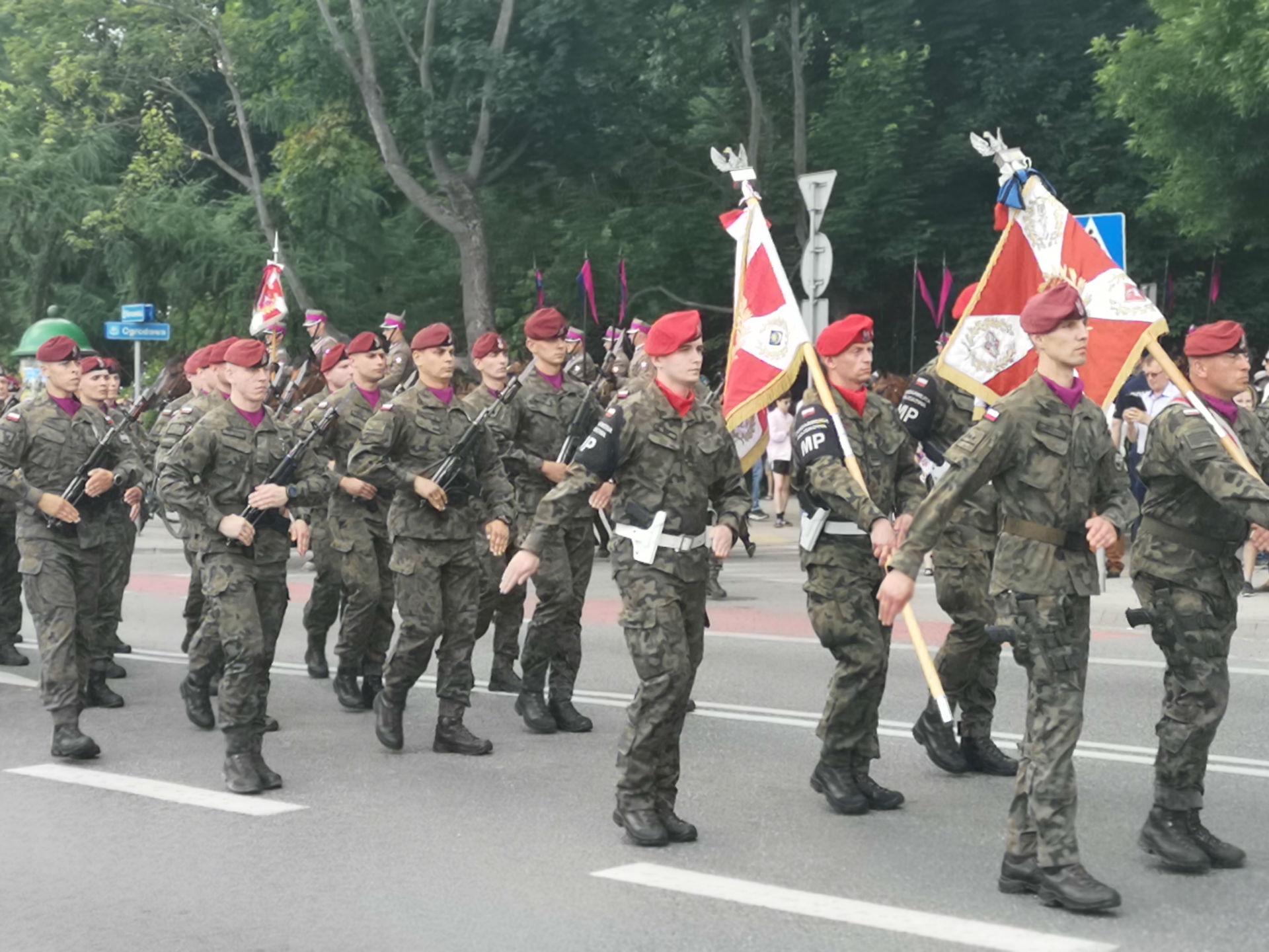 Parada z okazji obchodów 100-lecia przybycia 7 Pułku Ułanów Lubelskich do Mińska Mazowieckiego. Ulicą miasta idzie oddział żółnierzy w mundurach moro i czerwonych beretach. Niektórzy niosą karabiny oraz chorągwie.