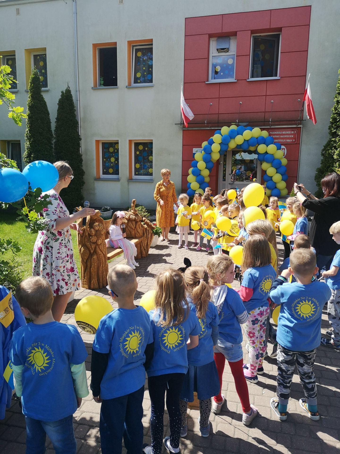 Fotografia wykonana przed przedszkolem miejskim nr 3. Dzieci ubrane w żółte i niebieskie podkoszulki otaczają półokręgiem drewnianą ławkę dekorowaną rzeźbiarsko, obok której stoi drugi zastępca burmistrza, Eliza Bujalska.