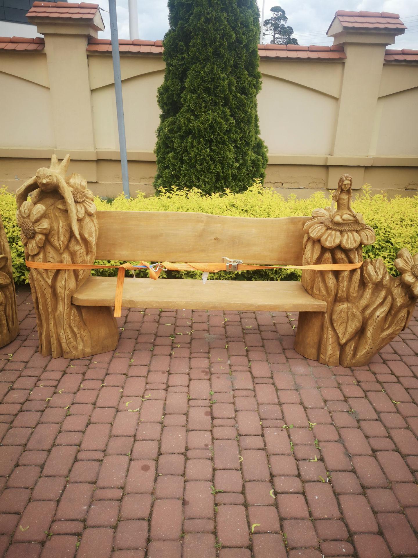 Zbliżenie na ławkę z poprzedniego zdjęcia, stojącą przed Muzeum 7 Pułku Ułanów Lubelskich. Z prawej i lewej strony posiada wkomponowane w jej konstrukcję przedstawienia kwiatów, ptaka oraz miniaturowej postaci ludzkiej.