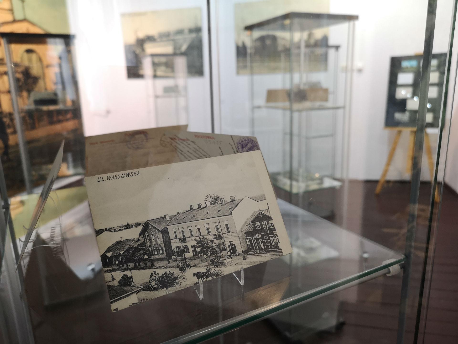 Wnętrze gabloty. Na pierwszym planie pocztówka z historycznym widokiem ul. Warszawskiej w Mińsku Mazowieckim. W tle reszta ekspozycji.
