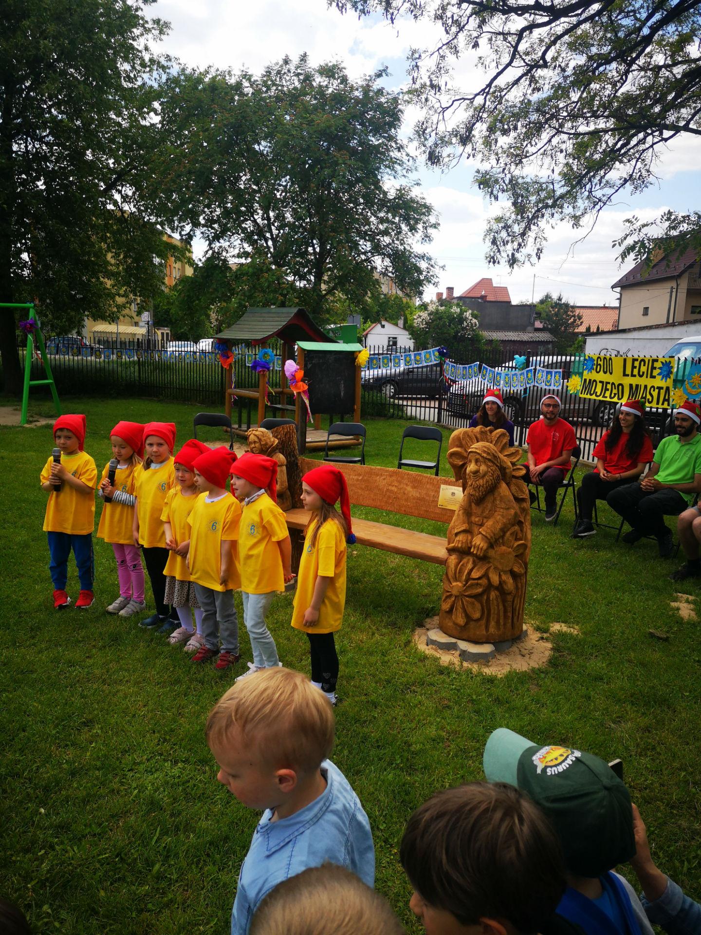 Fotografia wykonana przed przedszkolem miejskim nr 6. Na pierwszym planie dzieci w długich czerwonych czapkach stoją przed drewnianą ławką dekorowaną rzeźbiarsko postacią krasnoludka.