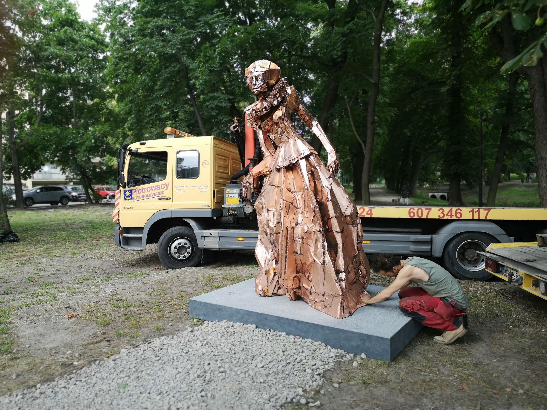 Pomnik Anny Mińskiej ustawiony na cokole, pozbawiony uprzęźy. Jeden mężczyzna dokonuje ostatnich poprawek łączenia z cokołem.