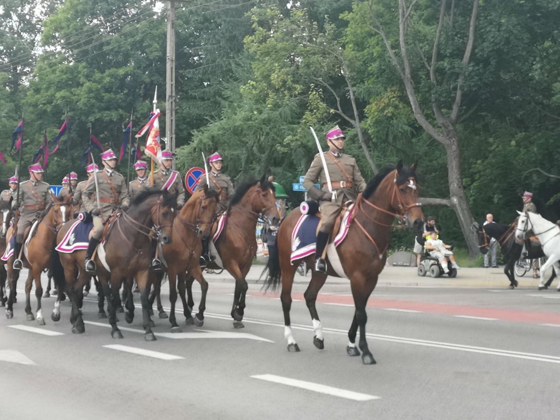 Parada z okazji obchodów 100-lecia przybycia 7 Pułku Ułanów Lubelskich do Mińska Mazowieckiego. Ulicą miasta jedzie zastęp kawalerii. Mężczyźni ubrani są w historyczne, zielone mundury, w rękach trzymają szable, na głowach mają rogatywki z fioletowym paskiem.
