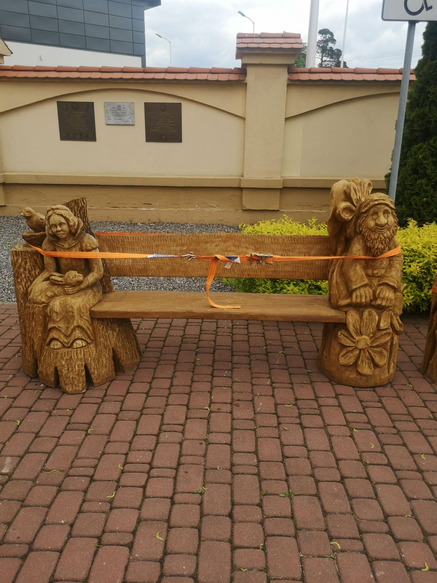 Zbliżenie na ławkę z poprzedniego zdjęcia, stojącą przed Muzeum 7 Pułku Ułanów Lubelskich. Z prawej i lewej strony posiada wkomponowane w jej konstrukcję przedstawienia odpowiednio krasnoludka oraz kobiety trzymającej na kolanach zająca.