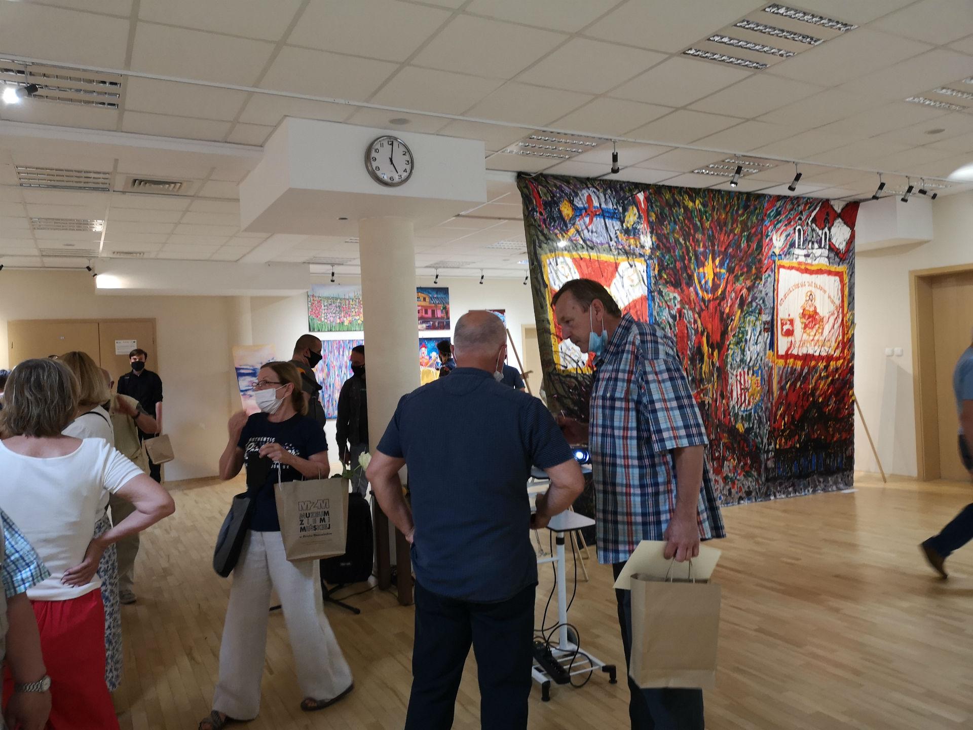 Fotografia wykonana w sali konferencyjno-wystawowej w Miejskiej Bibliotece Publicznej w Mińsku Mazowieckim. Lewą stronę oraz pierwszy plan kadru zajmują zwiedzający. Na drugim planie po prawej stronie wisi zawieszona jest monumentalna tkanina, na której namalowano obraz o tematyce patriotycznej.