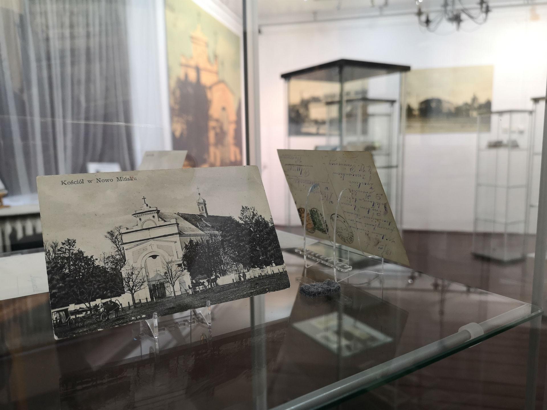 Wnętrze gabloty. Na pierwszym planie pocztówka z historycznym widokiem kościoła Najświętszej Maryi Panny w Mińsku Mazowieckim. W tle reszta ekspozycji.