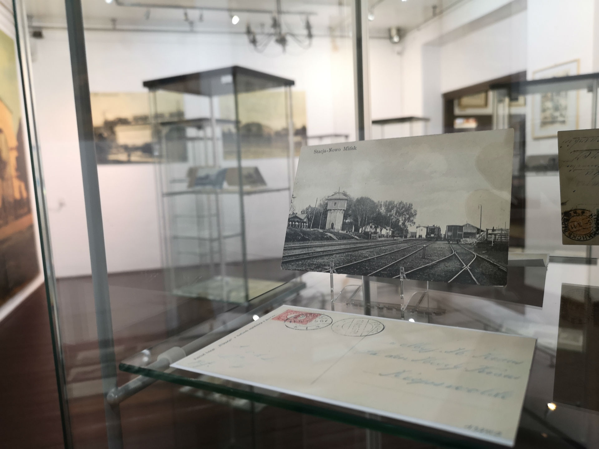 Wnętrze gabloty. Na pierwszym planie pocztówka z historycznym widokiem stacji kolejowej w Mińsku Mazowieckim. W tle reszta ekspozycji.