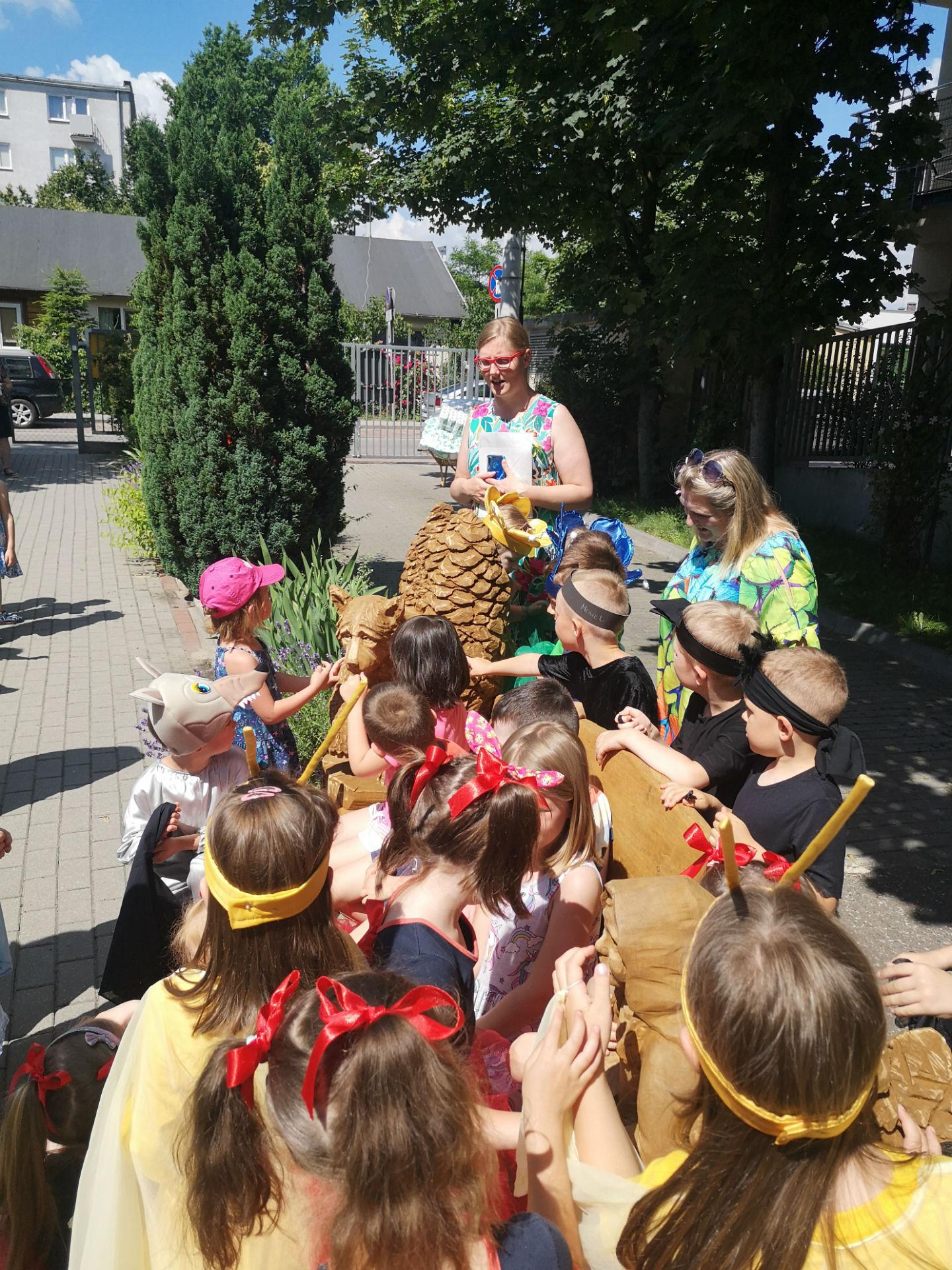 Fotografia wykonana przed przedszkolem miejskim nr 4. Na pierwszym planie dzieci ściśle otaczają drewnianą ławkę dekorowaną rzeźbiarsko motywami bajkowymi.