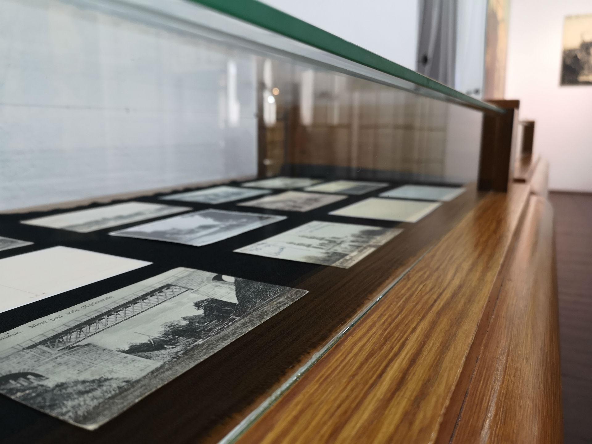 Wnętrze gabloty. Na pierwszym planie pocztówka z historycznym widokiem mostu kolejowego w Mińsku Mazowieckim. W tle reszta ekspozycji.