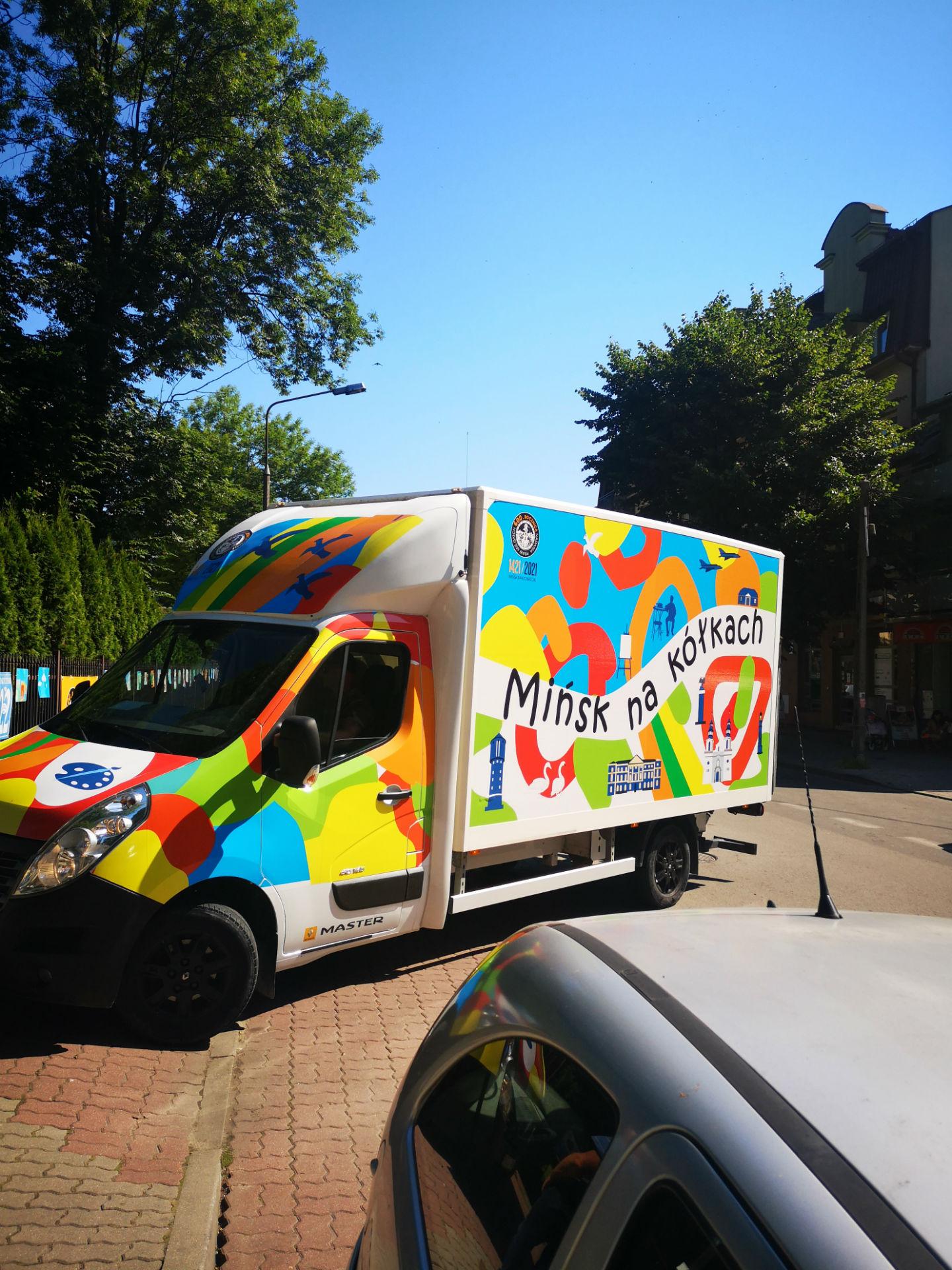 """Na zdjęciu pomalowana w żywe kolory ciężarówka z napisem """"Mińsk na kółkach"""" na boku."""