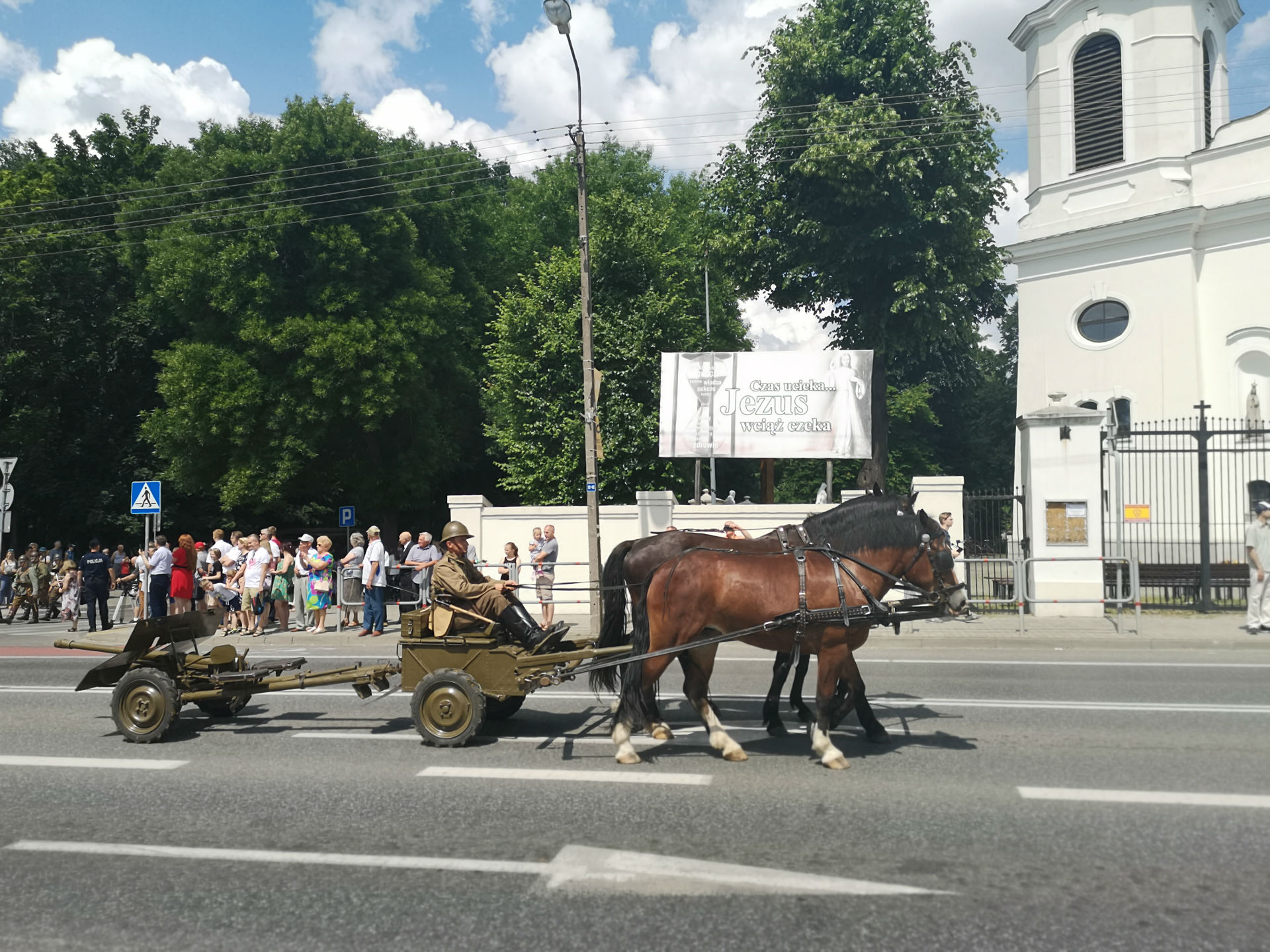 Parada z okazji obchodów 100-lecia przybycia 7 Pułku Ułanów Lubelskich do Mińska Mazowieckiego. Ulicą miasta jedzie żołnierz na specjalnym pojeździe do przewozu armaty ciągniętym przez dwa konie.