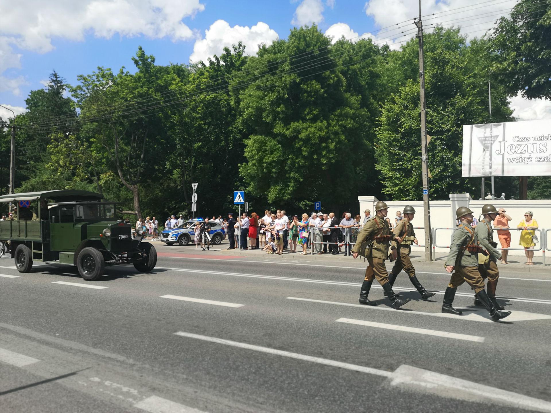 Parada z okazji obchodów 100-lecia przybycia 7 Pułku Ułanów Lubelskich do Mińska Mazowieckiego. Ulicą miasta idzie czterech żołnierzy ubranych w historyczne, zielone mundury; na głowach mają hełmy. Za nimi podąża zabytkowy samochód wojskowy.