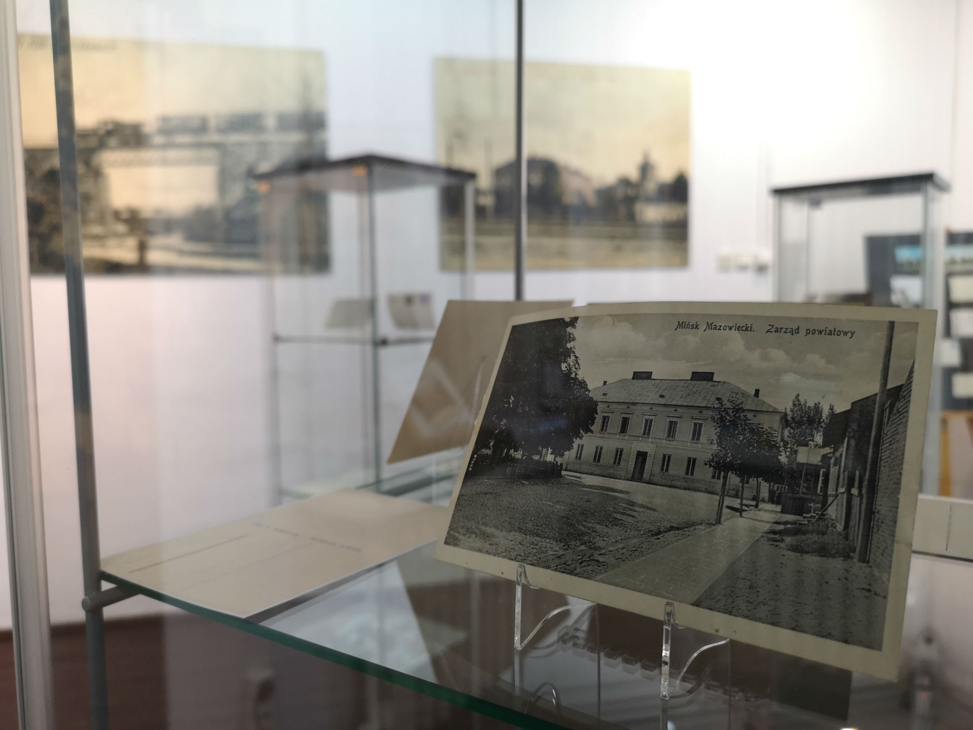 Wnętrze gabloty. Na pierwszym planie pocztówka z historycznym widokiem placu Kilińskiego w Mińsku Mazowieckim. W tle reszta ekspozycji.