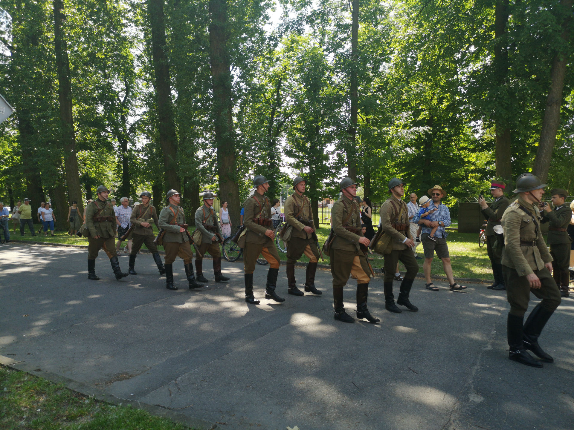 Parada z okazji obchodów 100-lecia przybycia 7 Pułku Ułanów Lubelskich do Mińska Mazowieckiego. W otoczeniu drzew ku prawej stronie kadru idzie zastęp żołnierzy ubranych w historyczne, zielone mundury; na głowach mają hełmy.