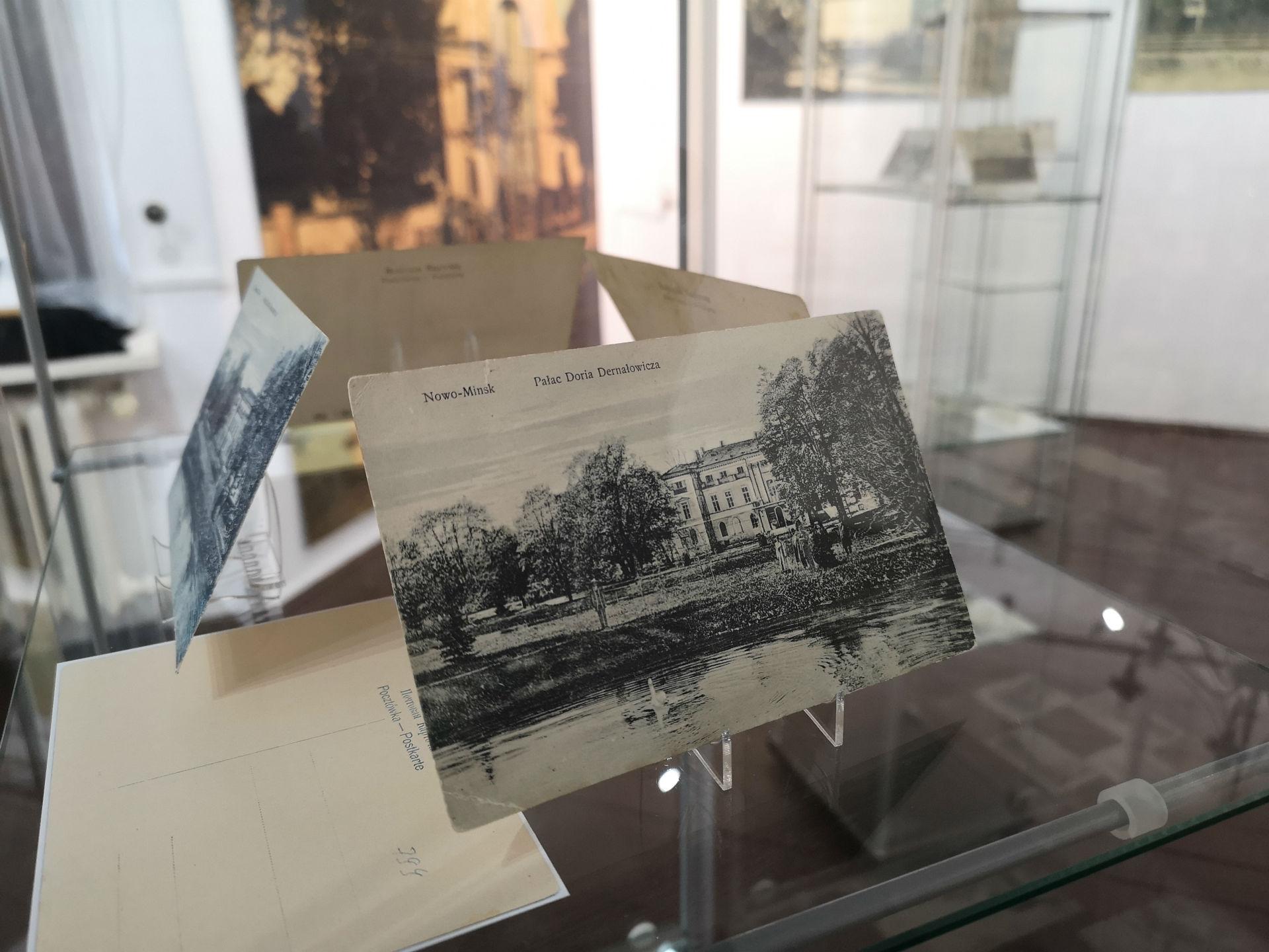 Wnętrze gabloty. Na pierwszym planie pocztówka z historycznym widokiem pałacu Dernałowiczów w Mińsku Mazowieckim. W tle reszta ekspozycji.